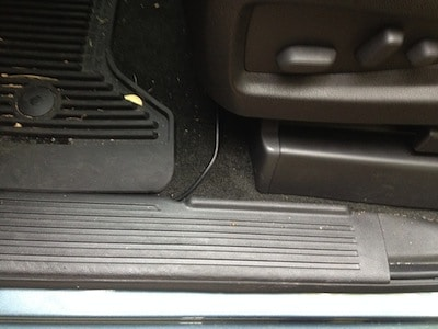 Cable runs under the plastic door trim and out under the driver seat on a GMC Sierra Pickup